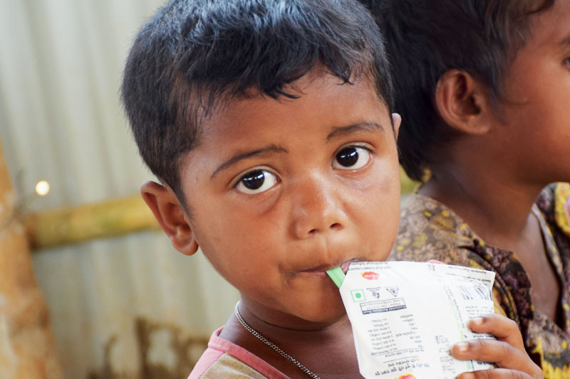 Rohingya child refugee eating a food ration