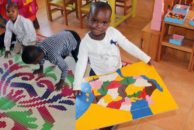 Child holding map of Tanzania - Sponsor a child in Tanzania