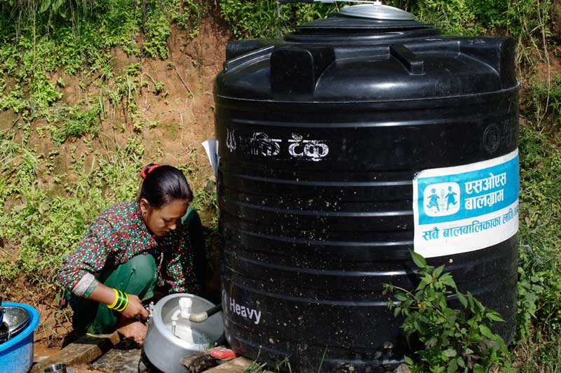 Woman getting water from water tank with SOS Nepal logo