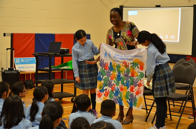 Olive Lumonya presenting a gift to students during her school visit.