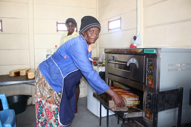 Wambi pulling fresh baked bread from the oven