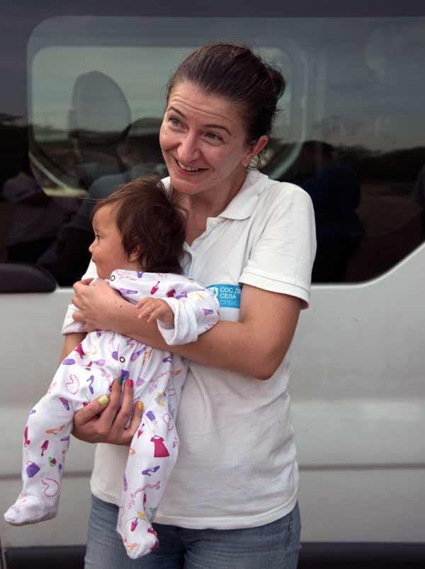 Katerina Ilievska holding infant migrant in Serbia
