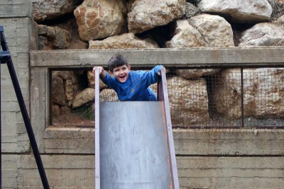 Boy playing on slide in Bhersaf, Lebanon