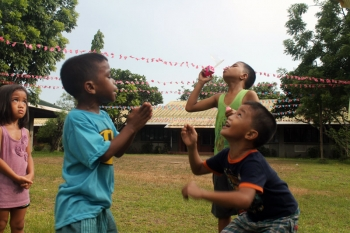 Sponsored SOS children playing and blowing bubbles in Manila, Philippines