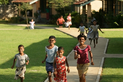 SOS sponsored children running through a field in the SOS Village in Monaragala, Sri Lanka