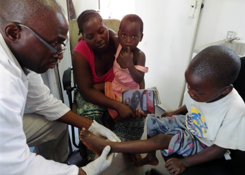 Doctor examining child's foot in Chipata, Zambia