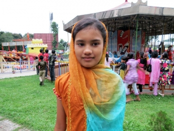 Bangladeshi girl standing in front of a merry-go-round