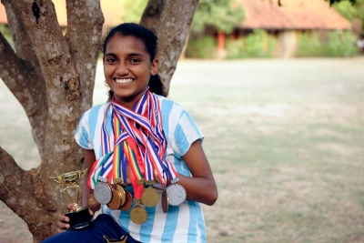 SOS sponsored child posing with her running medals in Anuradhapura, Sri Lanka