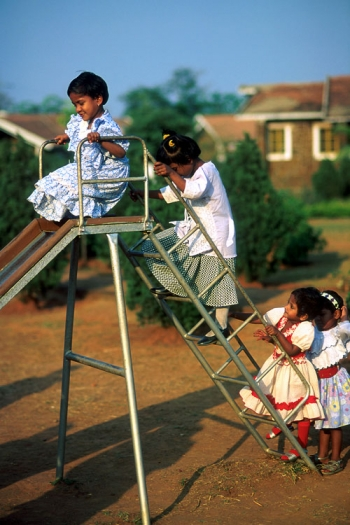 Girls in dresses using a slide in Rourkela, India