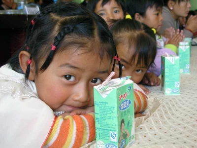 Two girls with drink boxes in Lhasa, China