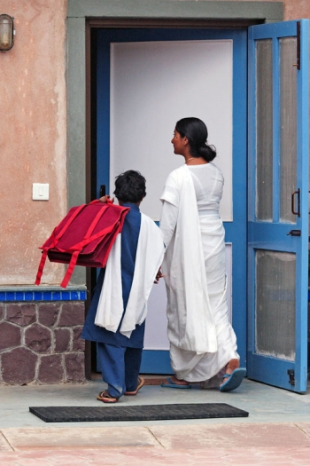 Mother welcoming child back from school in Khajuri Kalan, India