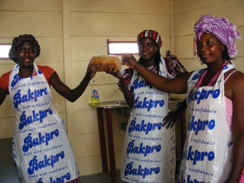 Women wearing aprons holding homemade bread in Ondangwa, Namibia