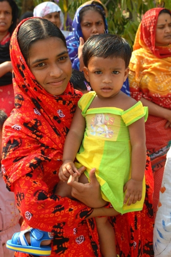 Youth holding a child in Khulna, Bangladesh