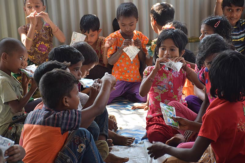 Rohingya refugee children eating food packets in the SOS Child Friendly Space in Bangladesh