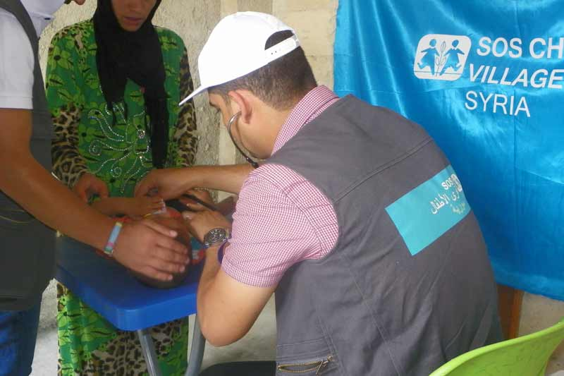 SOS doctor providing care to Syrian infant