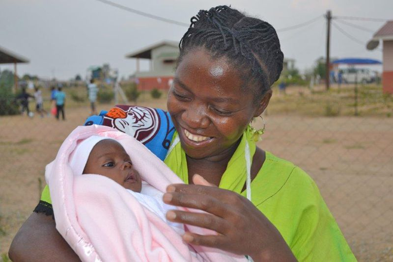 SOS mother holding sponsored infant child in Angola