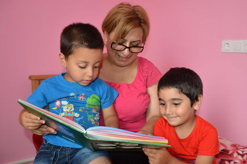 SOS mother reading with her two children in Armenia