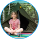 Girl sitting in front of tent at summer camp in Belarus
