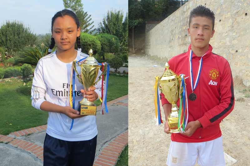 Nepalese girl and boy each with a soccer trophy