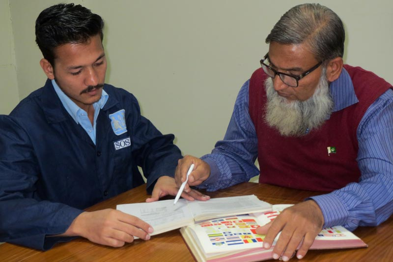 Teacher and student studying together in the Vocational Training Centre in Karachi, Pakistan