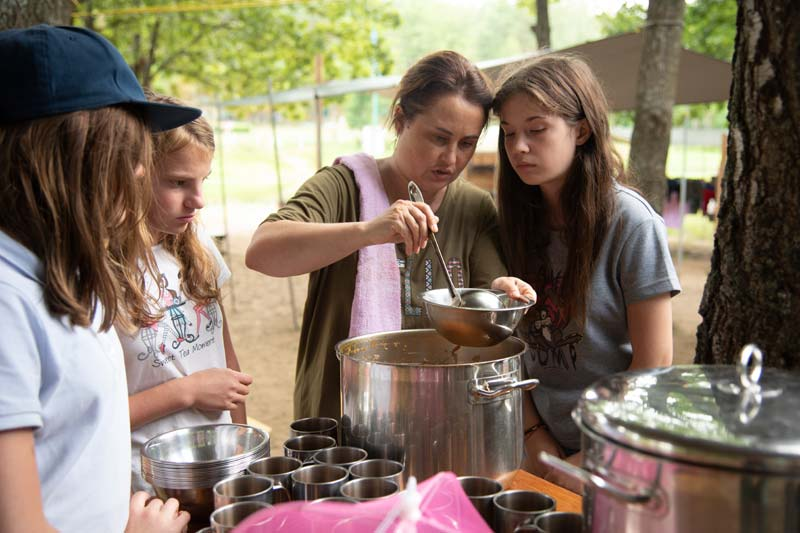 Teenagers helping to serve food at summer camp in Belarus