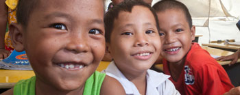 Three boys smiling in Tacloban, Philippines