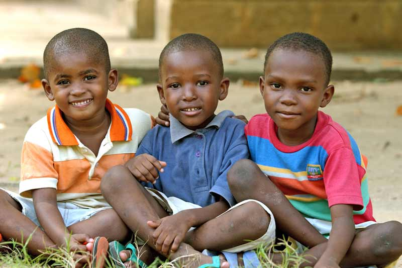 Three sponsored boys smiling in Tanzania