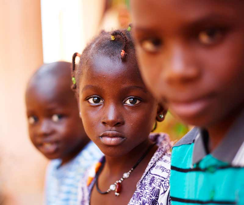 Three children sitting in row in Mali