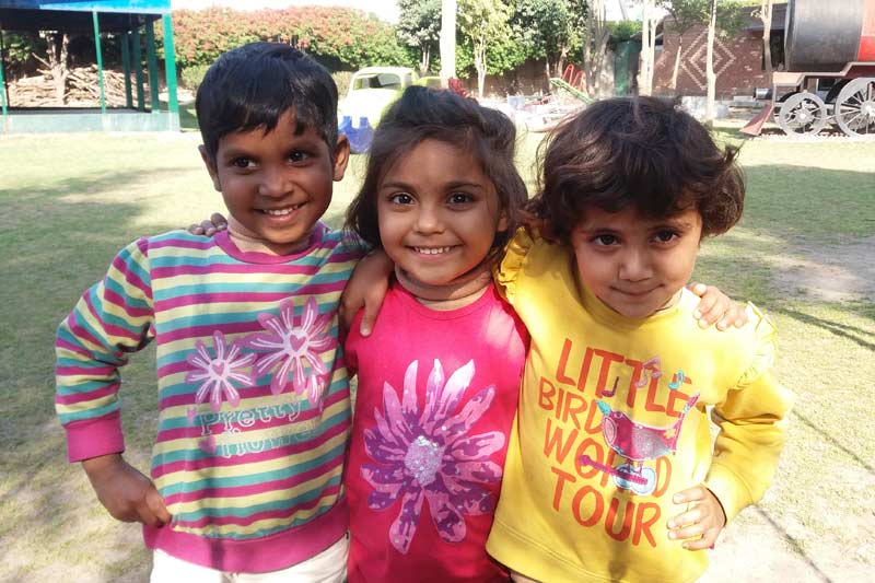 Three children smiling in Pakistan