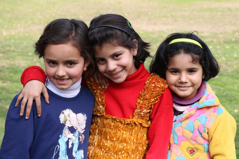 Three girls in a field in Pakistan smiling