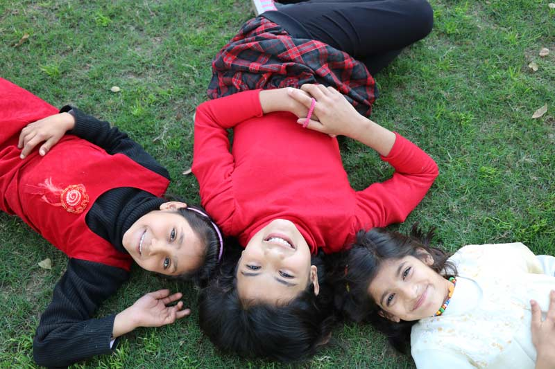 Three Pakistani girls laying on the grass