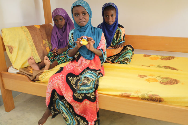 Rara sitting on a bed with her SOS siters in Tadjourah, Djibouti