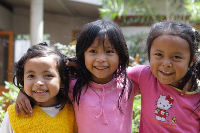 Three girls smiling in San Juan Sacatepéquez, Guatemala