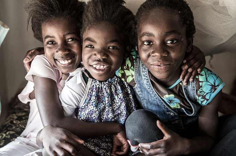 Three sisters smiling in the SOS Village in Lusaka, Zambia