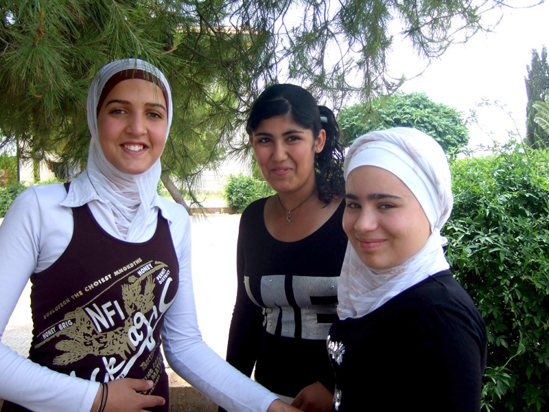 Three young women chatting in a garden in Aleppo, Syria