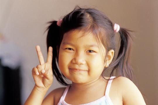 Orphan child making a peace sign