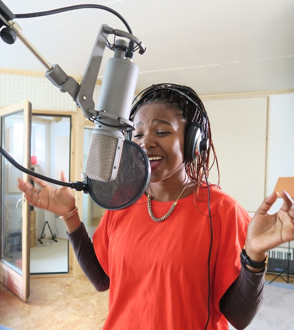 """Tumi singing her song """"Thank You"""" at a recording studio."""