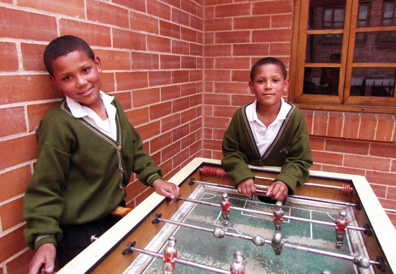 Two sponsored boys standing next to a foosball table in Colombia
