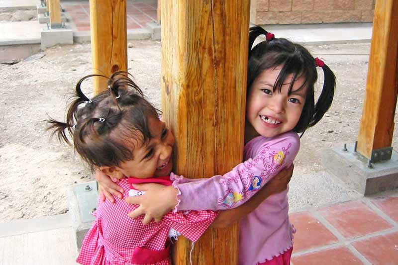 Two sponsored children hugging a post in El Salvador