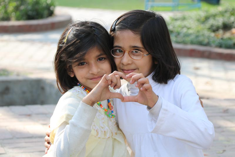 Two girls using fingers to make a heart in Pakistan