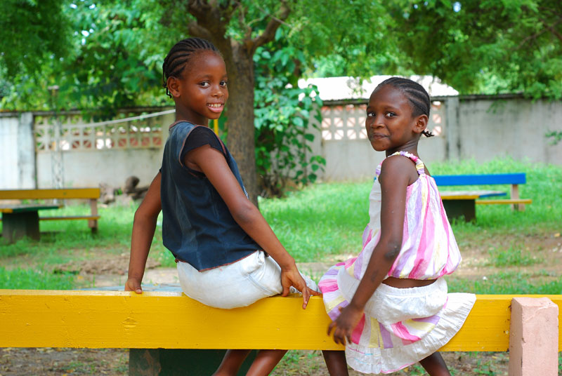 Two girl friends sitting on a bench in Bakoteh, Gambia