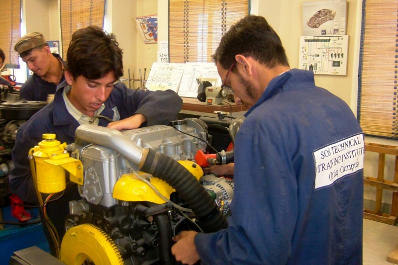 Two young men working on an engine in the Vocational Training Centre in Karachi