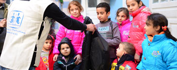 SOS volunteer handing out winter jackets in Damascus, Syria