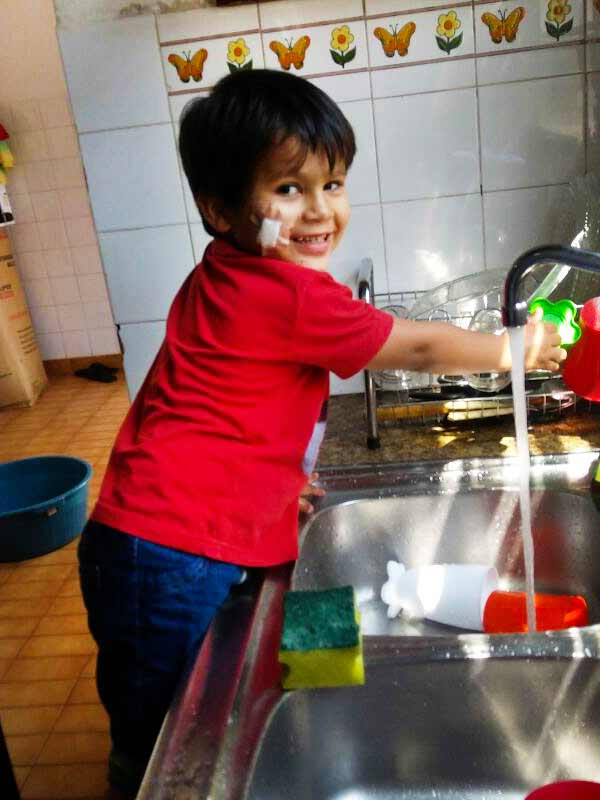Young boy doing dishes in San Ignacio, Paraguay